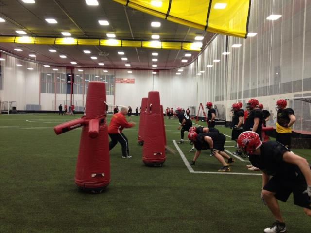Coach Cluff working with his d-linemen in the Gryphon Fieldhouse