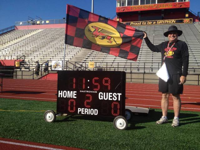 Coach Lang poses with flag and the clock/timer that keeps practices moving at a brisk pace