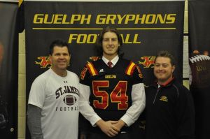 LB recruit Mark McCormack with his St James' coaches