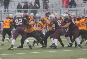 Gryphon OLs walling off  the GeeGees D-Line as Jazz rolls out the other way