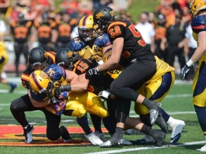 Gryphon D swarms Queen's RB Photo: Rob Massey/Guelph Mercury