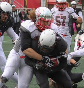 John Rush stops Carleton ball carrier Photo: Lou Toppan